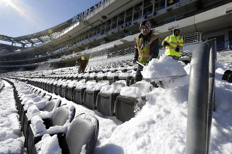 Workers shovel snow off the seating area at MetLife Stadium as crews removed snow ahead of Super Bowl XLVIII following a snow storm, Wednesday, Jan. 22, 2014, in East Rutherford, N.J. Super Bowl XLVIII, which will be played between the Denver Broncos and the Seattle Seahawks on Feb. 2, will be the first NFL title game held outdoors in a city where it snows. (AP Photo/Julio Cortez)
