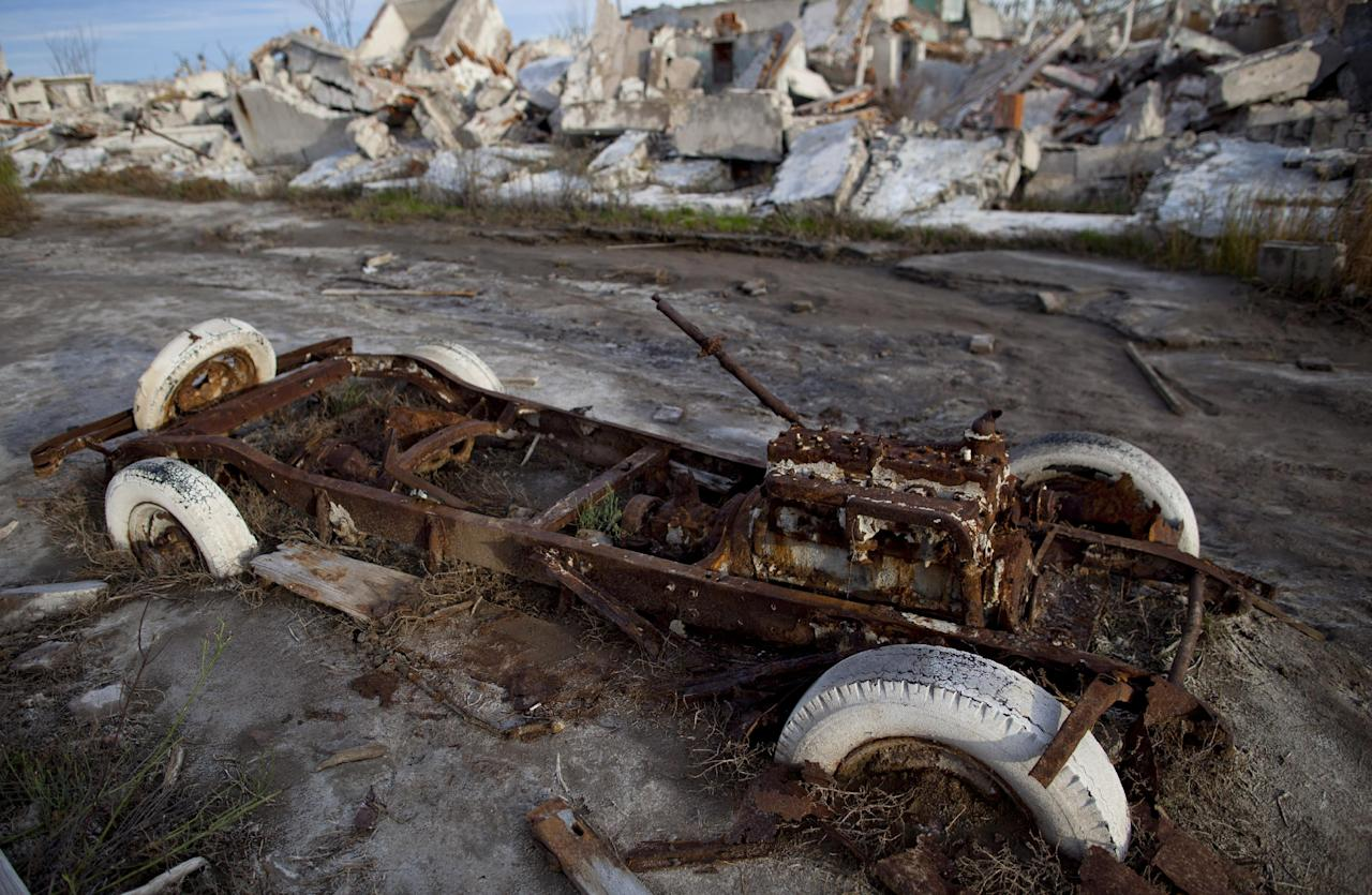 In this May 7, 2013 photo, a car sits in ruins in Epecuen, a village that once was submerged in water in Argentina. People come to see the rusted hulks of automobiles and furniture, crumbled homes and broken appliances. They climb staircases that lead nowhere, and wander through a graveyard where the water toppled headstones and exposed tombs to the elements. (AP Photo/Natacha Pisarenko)