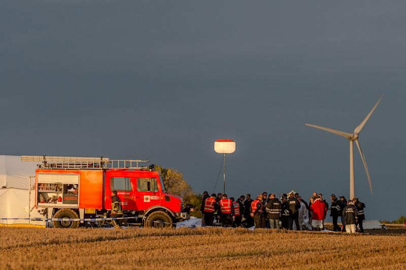 Rescue personnel work around the debris of a small plane which crashed in a field in Marchovelette, Belgium on Saturday, Oct. 19, 2013. The plane, carrying parachutists for a skydiving trip, crashed killing all 11 people aboard, officials said. (AP Photo/Geert Vanden Wijngaert)