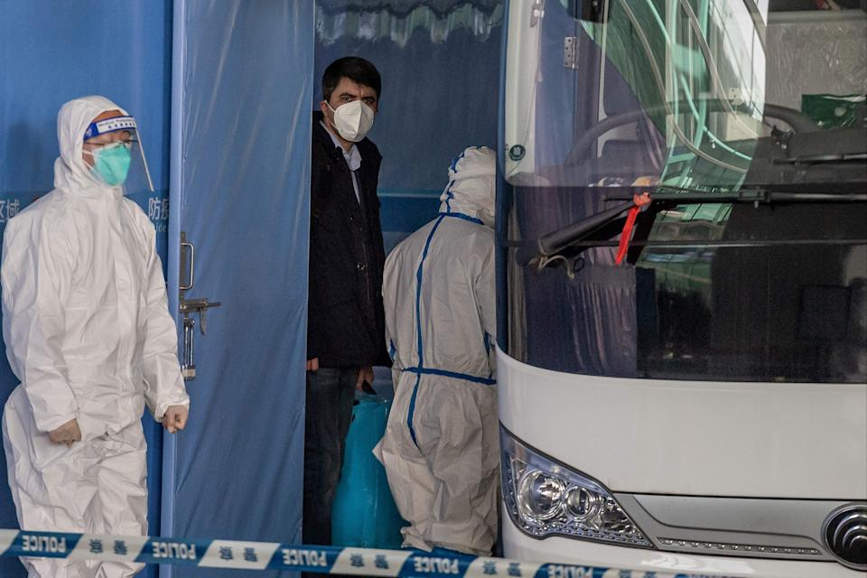 A member of the World Health Organization (WHO) team investigating the origins of the pandemic boards a bus following their arrival in Wuhan  (AFP via Getty Images)