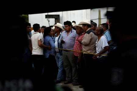 Supporters of slain mayoral candidate Santana Cruz Bahena stand at a crime scene outside his home in the municipality of Hidalgotitlan, in the state of Veracruz, Mexico November 20, 2017. REUTERS/Angel Hernandez
