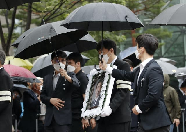A man carries a portrait of late Seoul Mayor Park Won-soon after his official funeral outside Seoul City Hall (Lee Jin-man/AP)