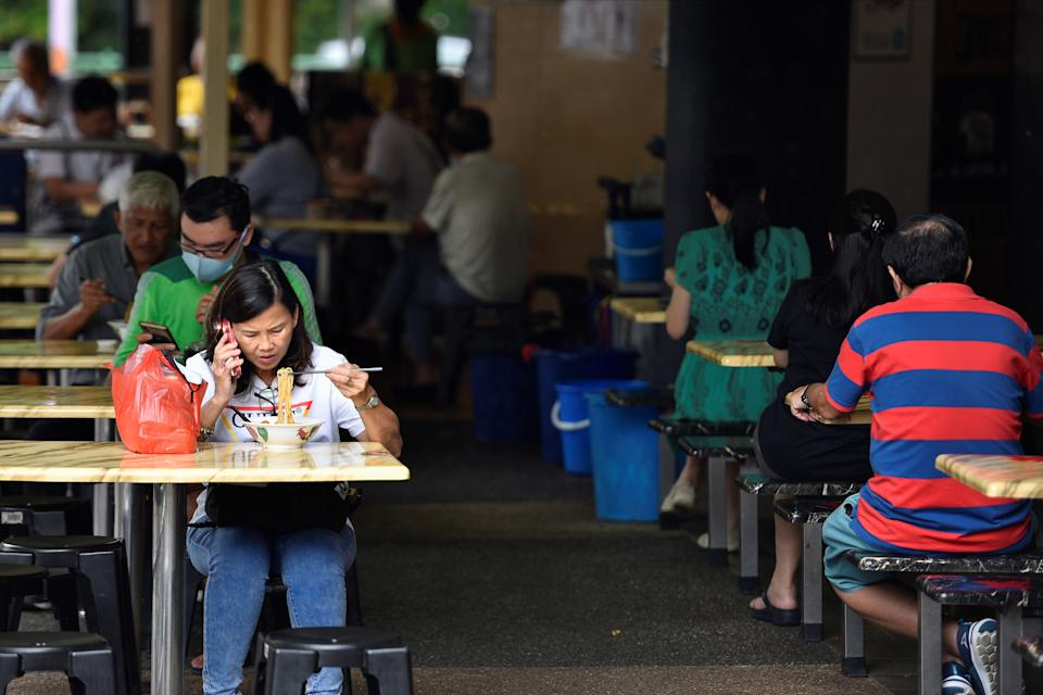 People eat outdoors before restrictions on outdoor dining kicks in on Sunday, due to the surge in coronavirus disease (COVID-19) cases in Singapore May 14, 2021. REUTERS/Caroline Chia