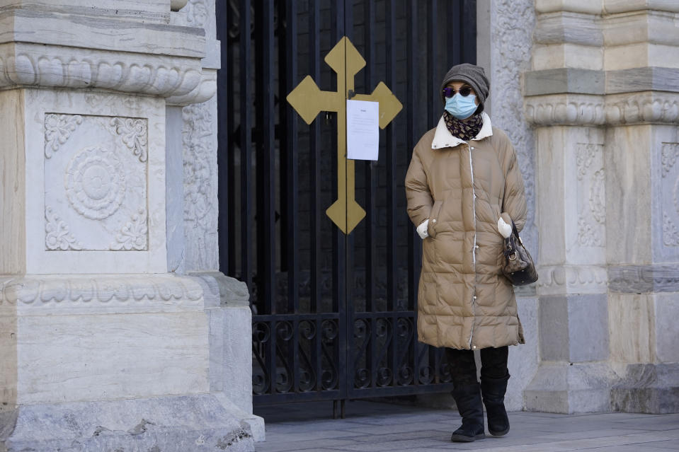 A visitor wearing mask to protect from the coronavirus walks by a closure notice outside outside the Wangfujing Church in Beijing on Friday, Dec. 25, 2020. Official churches in the Chinese capital abruptly cancelled mass on Christmas day in a last-minute move owing to the pandemic. The capital city is on high alert after new confirmed COVID-19 cases were reported last week and new asymptomatic cases reported Christmas day. (AP Photo/Ng Han Guan)
