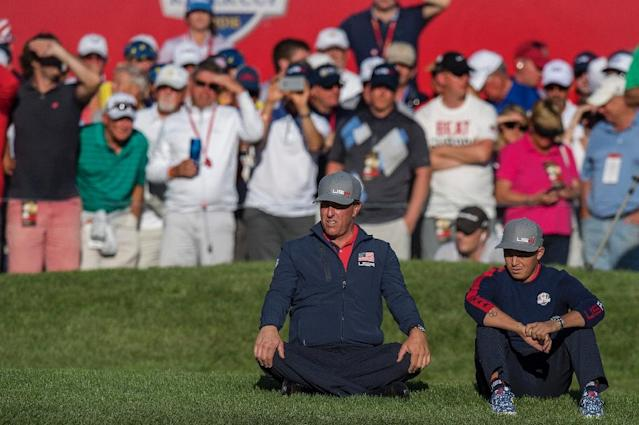 Team USA's Phil Mickelson (C) and Ricky Fowler sit on the grass as they watch their teammates play the afternoon four-balls matches during the 2016 Ryder Cup, at Hazeltine National Golf Course in Chaska, Minnesota, on September 30 (AFP Photo/Jim Watson)