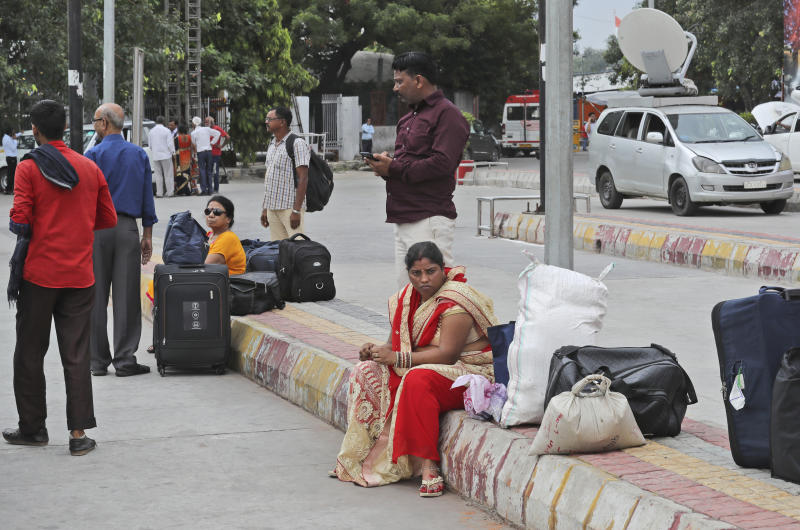 Passengers wait for transportation during a public transport strike in New Delhi, India, Thursday, Sept. 19, 2019. Commuters in the Indian capital are facing problems as a large section of the public transport, including private buses, auto-rickshaws and a section of app-based cabs Thursday remained off the roads in protest against a sharp increase in traffic fines imposed by the government under a new law.(AP Photo/Manish Swarup)