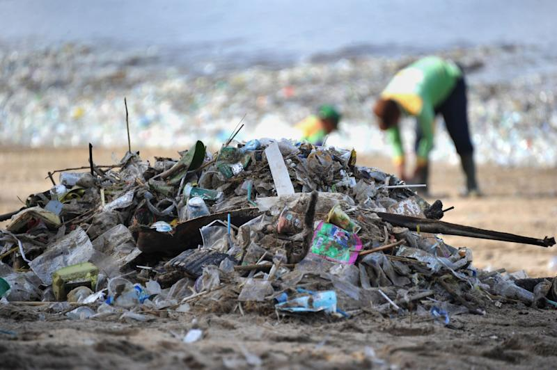 Workers remove litter from a popular beach in Bali - AFP