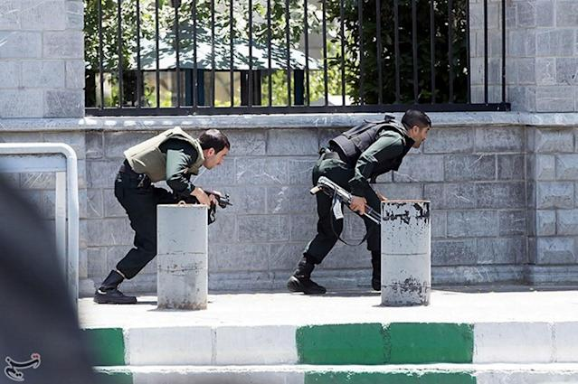 <p>Members of Iranian forces take cover during an attack on the Iranian parliament in central Tehran, Iran, June 7, 2017. (Photo: Tasnim News Agency/Handout via Reuters) </p>