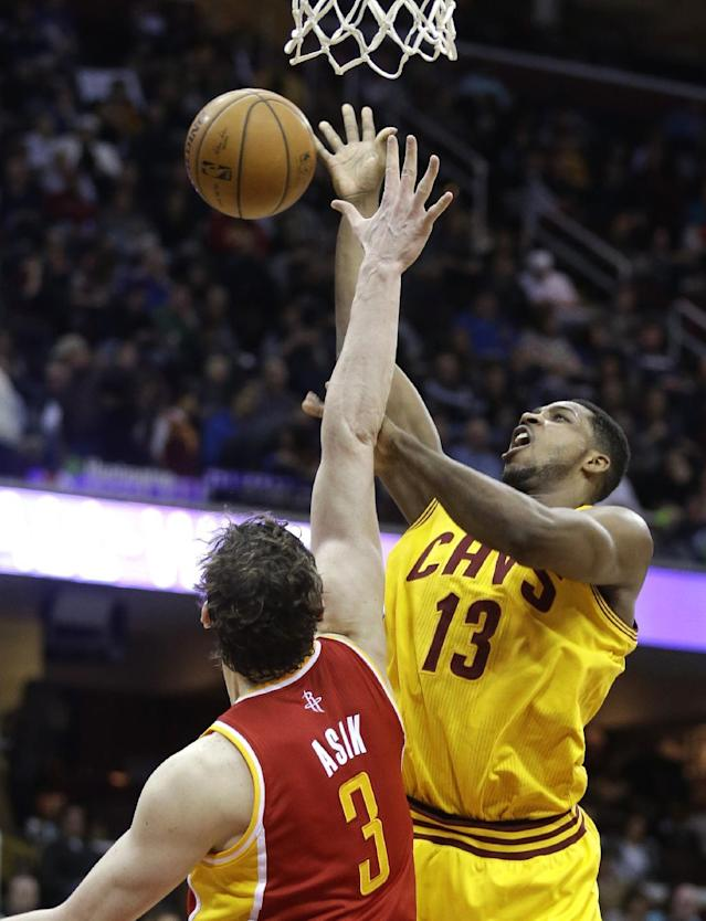 Cleveland Cavaliers' Tristan Thompson (13), from Canada, loses control of the ball under pressure from Houston Rockets' Omer Asik (3), from Turkey, during the second quarter of an NBA basketball game, Saturday, March 22, 2014, in Cleveland. (AP Photo/Tony Dejak)