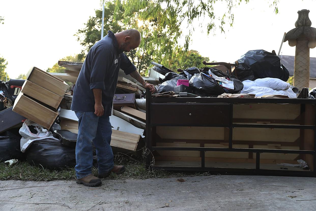 Ernesto Ramirez pauses as he cleans out his house.