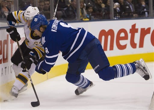 Toronto Maple Leafs defenceman Mike Komisarek, right, gets tripped up by Boston Bruins forward Brad Marchand, left, during first period NHL hockey action in Toronto on Tuesday, March. 6, 2012. (AP Photo/The Canadian Press, Nathan Denette)