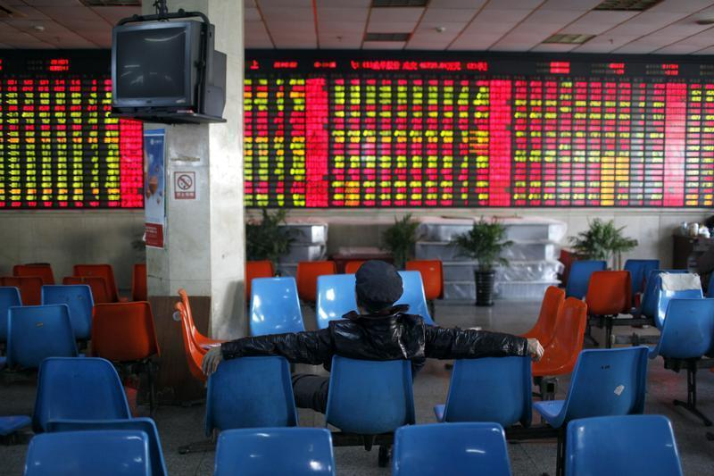 An investor sits in front of an electronic board showing stock information at a brokerage house in Shanghai