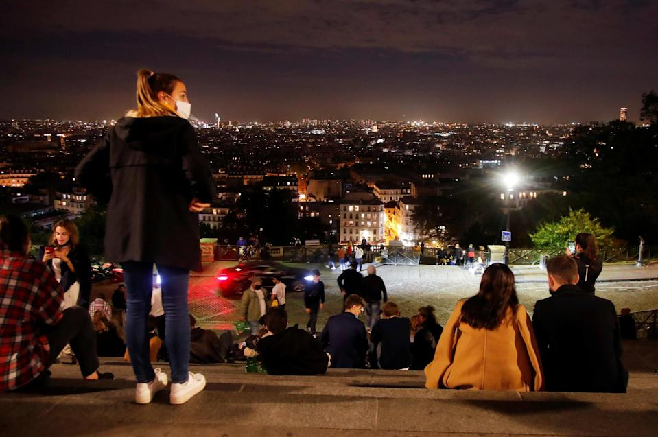 People enjoy the view from Montmartre in Paris before the nightly curfew: REUTERS