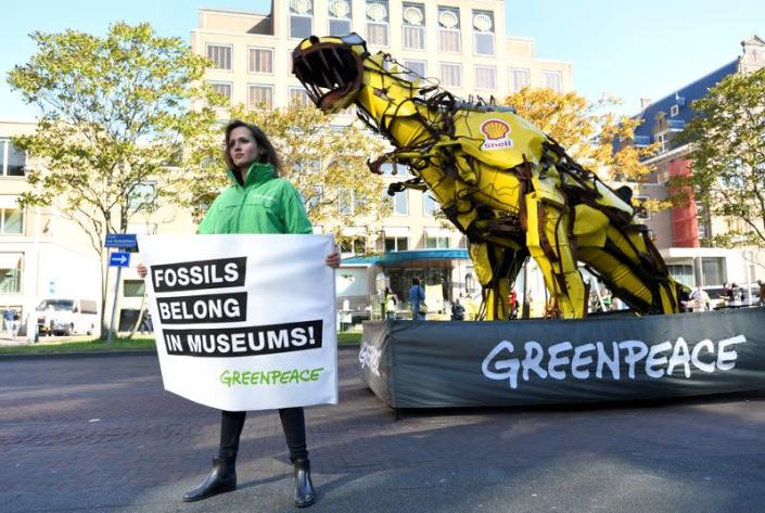 Protester holds a banner during a demonstration outside of the Shell headquarters, in The Hague