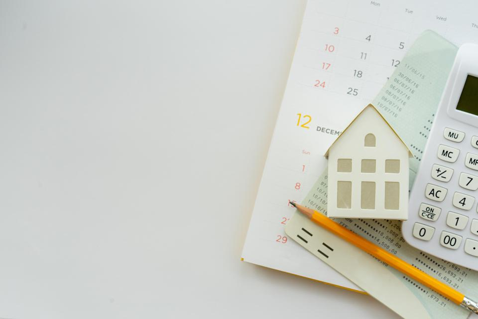 close up top view of a group of calculator, home model, yellow pencil, bank ledger and calendar on white colored background with space for money management, home loan and personal finance concept - Credit: chinnarach - stock.adobe.com