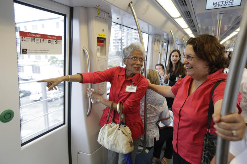 In this Wednesday, April 2, 2014 photo, government employees and their guests ride on a subway while participating in an invitation to test the wagons of the new Panama Metro in Panama City. Central America's first underground metro will surely alleviate the booming capital's dreadful traffic. But critics say the $2 billion spent on the 14-kilometer rail project, which was marred by cost overruns, would've been better used building a higher-capacity, surface transport network. They also are blasting the timing of the over-the-top inauguration set for Saturday, April 5, which they say is a political stunt by President Ricardo Martinelli to drum up support for his preferred successor. (AP Photo/Arnulfo Franco)