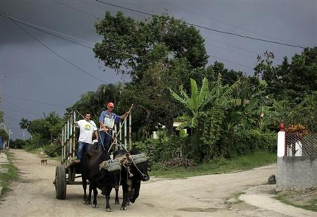 Farmers ride their oxen-pulled cart on the outskirts of Havana