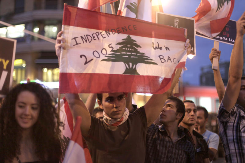 A Lebanese anti-government protester holds a national flag in Sassine Square, just steps away from the site where Brig. Gen. Wissam al-Hassan was assassinated Friday in a car bomb attack, in Beirut, Lebanon, Wednesday, Oct. 24, 2012. Lebanon's main opposition bloc blamed the Syrian regime on Wednesday for the killing of a top intelligence officer and demanded the current government, dominated by Syrian ally Hezbollah, resign.(AP Photo/Maya Alleruzzo)