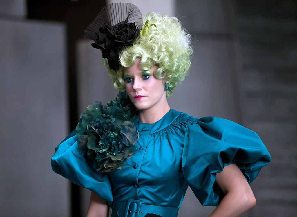 <p>The quirky Capitol escort, tasked with guiding Peeta and Katniss through their Hunger Games ceremonies, switches it up to turquoise and black, with a bright blond wig, in a scene where she admonishes Katniss for firing an arrow toward Capitol leaders.</p>
