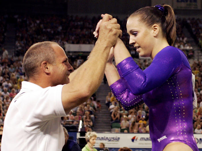 FILE - Chellsie Memmel is congratulated by her coach and father, Andrew Memmel, after completing her routine on the Floor Exercise in the final of the Women's Individual All-Around at the World Gymnastic Championships in Melbourne, Australia, in this Nov. 25, 2005 file photo. Memmel started doing gymnastics again when the COVID-19 pandemic hit last spring because it felt like one of the few things in her life she could control. The 32-year-old former world champion and Olympic silver medalist discovered more than an outlet for stress. She rediscovered her love for the sport, so much so the married mother of two is making an unlikely comeback. AP Photo/Mark Baker, File)
