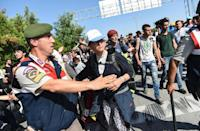 A Turkish police officer gestures to colleagues as Syrian migrants and refugees march along the highway towards the Turkish-Greek border at Edirne on September 18, 2015 (AFP Photo/Bulent Kilic)