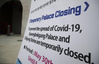 A sign of temporarily closure is displayed in front of Gwanghwamun, the main gate of the 14th-century Gyeongbok Palace, and one of South Korea's well-known landmarks, in Seoul, South Korea, Friday, June 19, 2020. (AP Photo/Lee Jin-man)