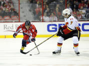 Washington Capitals left wing Alex Ovechkin (8), of Russia, battles for the puck against Calgary Flames defenseman T.J. Brodie (7) during the first period of an NHL hockey game, Tuesday, Nov. 4, 2014, in Washington. (AP Photo/Nick Wass)