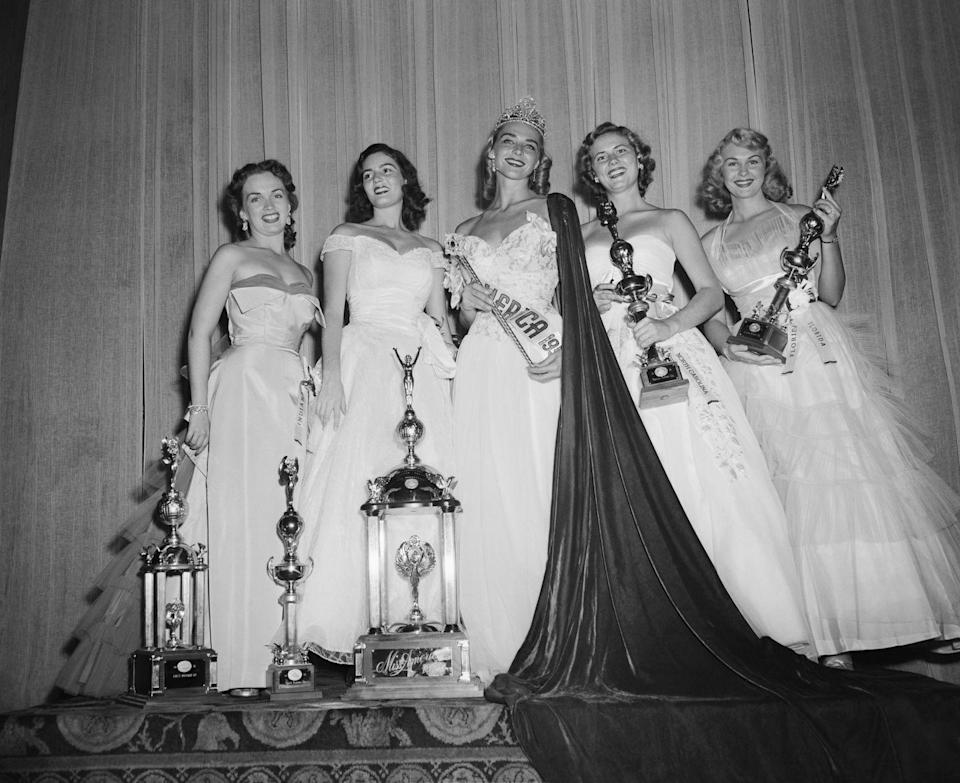 <p>Colleen Hutchins from Utah, center, is pictured next to the runners-up following her win. Her white off-the-shoulder gown is fit for a bride.</p>