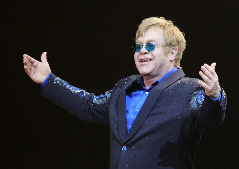 """FILE- In this Friday, Nov. 23, 2012, file photo, Elton John greets the audience during his concert at the Mercedes-Benz Arena in Shanghai, China. The Luddite label has been applied to everyone from anti-technology extremists to those who merely struggle with technology or don't want to bother with it to extremists. """"I'm a Luddite,'' pop star Elton John told the Britain's The Telegraph newspaper in 2011. """"I don't have a phone. I don't have a computer. I don't have an iPad. And I don't have an iPod.'''(AP Photo/Eugene Hoshiko)"""
