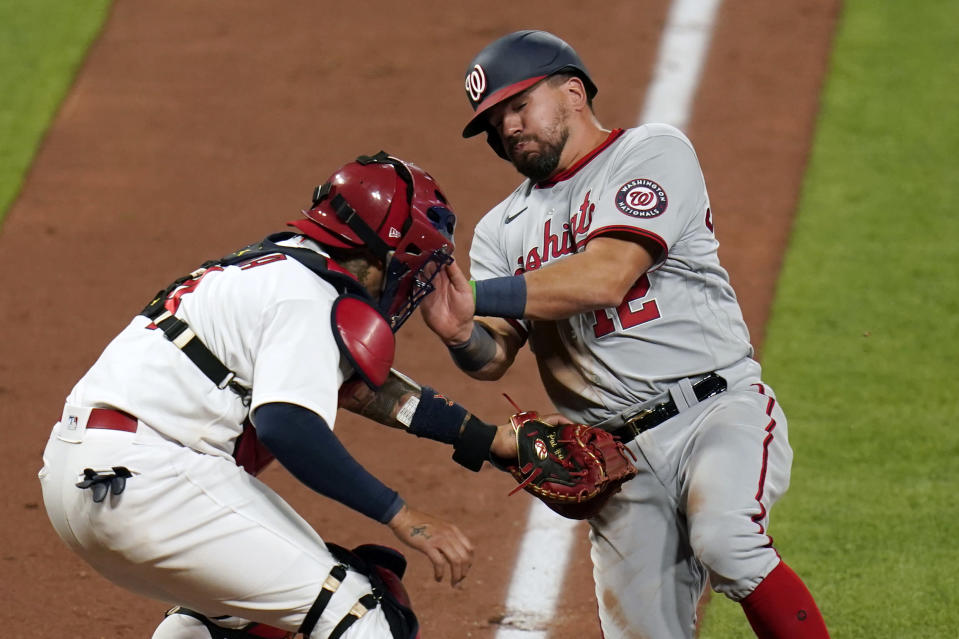 Washington Nationals' Kyle Schwarber, right, is tagged out at home by St. Louis Cardinals catcher Yadier Molina to end the top of the eighth inning of a baseball game Monday, April 12, 2021, in St. Louis. (AP Photo/Jeff Roberson)