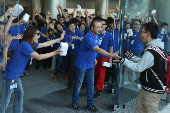 BEIJING, CHINA - OCTOBER 20:  Chinese Apple staff members greet customers as they enter the new Apple Store in Wangfujing shopping district on October 20, 2012 in Beijing, China. Apple Inc. opened its sixth retail store on the Chinese mainland Saturday. The new Wangfujing store is Apple's largest retail store in Asia.  (Photo by Feng Li/Getty Images)