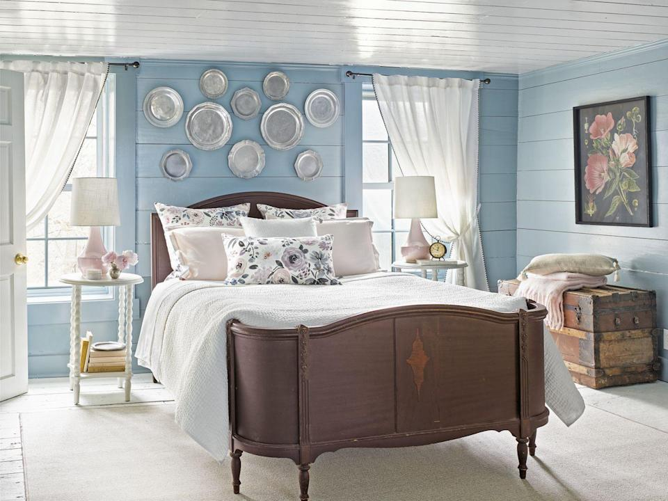 """<p>Singer-songwriter—and serial renovator—Holly Williams enveloped her master bedroom in a soothing watery blue. Painting the ceiling a glossy white helps visually """"raise"""" the small bedroom's low ceiling height—a common issue with old farmhouses. </p><p><strong>Get the Look:<br></strong>Wall Paint Color: <a href=""""https://www.benjaminmoore.com/en-us/color-overview/find-your-color/color/HC-145/van-courtland-blue?color=HC-145"""" rel=""""nofollow noopener"""" target=""""_blank"""" data-ylk=""""slk:Van Courtland Blue by Benjamin Moore"""" class=""""link rapid-noclick-resp"""">Van Courtland Blue by Benjamin Moore</a><br>Ceiling Paint Color: <a href=""""https://www.ppgpaints.com/color/color-families/neutrals/delicate-white"""" rel=""""nofollow noopener"""" target=""""_blank"""" data-ylk=""""slk:Delicate White by PPG Porter Paint"""" class=""""link rapid-noclick-resp"""">Delicate White by PPG Porter Paint</a></p>"""
