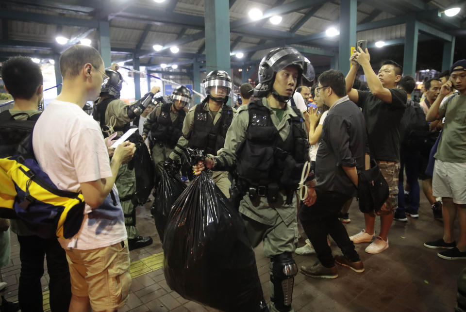 Police officers carry plastic bags containing items confiscated during search at central ferry pier in Hong Kong, Sunday, Sept. 1, 2019. Train service to Hong Kong's airport was suspended Sunday as pro-democracy demonstrators gathered there, while protesters outside the British Consulate called on London to grant citizenship to people born in the former colony before its return to China. (AP Photo/Jae C. Hong)