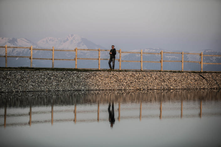 In this image take on Thursday, April 23, 2020 Lorenzo Pasinetti, 53, poses by an artificial lake near his chalet 'Baita Termen', at Monte Pora, near Bergamo, northern Italy. His chalet has a restaurant, a pizzeria a cafe' and an outdoor barbeque, catering for some 2000 people a day in the winter a day and 300 in the summer. After Italy's national lockdown since March 8, he calculated a loss of about 60% compared to the year before. to March last year his loss was about 60%. During the restriction measures he stayed open to provide some 10 families living on the mountain with their groceries. (AP Photo/Luca Bruno)