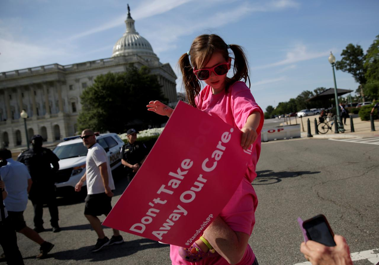 A girl is carried as healthcare activists with Planned Parenthood and the Center for American Progress protest in opposition to the Senate Republican healthcare bill on Capitol Hill in Washington, U.S., June 28, 2017.   REUTERS/Joshua Roberts