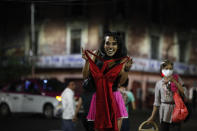 """Sex worker Geraldine, wearing cat make-up, excitedly holds up a dress she is thinking of buying from a street vendor, so that her partner, sitting nearby to keep her company, can see it, as she waits for clients outside the Revolution subway station, in Mexico City, Saturday, March 13, 2021. According to Geraldine, 30, the pandemic has cut clients and increased risks to the sex workers but has also brought out more assistance for them too, both from dedicated organizations such as the activist group Brigada Callejera or """"The Street Brigade"""" and from individuals who have donated food or clothing. (AP Photo/Rebecca Blackwell)"""
