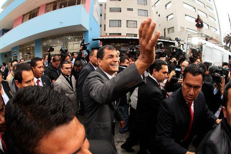 Rafael Correa (C) waves after voting a polling station in Quito on February 17, 2013