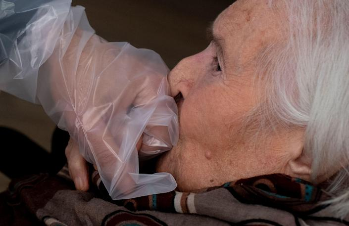"""A resident of the Villa Sacra Famiglia nursing home in Rome kisses the hand of her grandson through a plastic screen in a """"Hug Room"""" on March 3 amid the COVID-19 pandemic."""