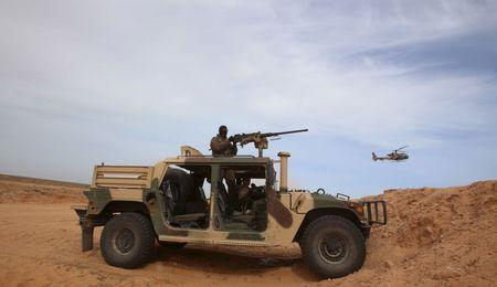 A Tunisian soldier holds his position during an exercise along the frontier with Libya in Sabkeht Alyun