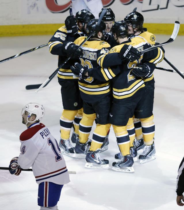 Boston Bruins center Carl Soderberg is surrounded by teammates after scoring against Montreal Canadiens goalie Carey Price during the first period of Game 5 in the second-round of the Stanley Cup hockey playoff series in Boston, Saturday, May 10, 2014. Canadiens center Tomas Plekanec (14) skates by. (AP Photo/Charles Krupa)