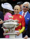 Jockey Mike Smith holds the August Belmont trophy after winning the Triple Crown and the 150th running of the Belmont Stakes horse race aboard Justify, Saturday, June 9, 2018, in Elmont, N.Y. Trainer Bob Baffert is at right. (AP Photo/Frank Franklin II)