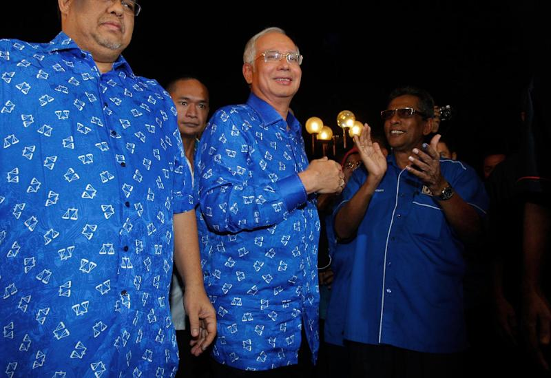 Malaysian Prime Minister Najib Razak, center, arrives at his ruling National Front coalition's headquarters in Kuala Lumpur, Malaysia, Sunday, May 5, 2013. Malaysia's ruling coalition took an early lead in results for national elections Sunday after a record number of voters cast ballots, with some choosing to extend the coalition's 56-year rule and others pressing for an unprecedented victory by an opposition that pledges cleaner government. (AP Photo/Lai Seng Sin)