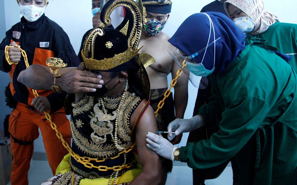 A healthcare worker injects a dose of Sinovac's vaccine to a man dressed in Indonesia's traditional human puppet costume known as 'Wayang', as Indonesia drives mass vaccination for the coronavirus at a hospital in Solo, Central Java province, - Reuters/Antara Foto/Maulana Surya