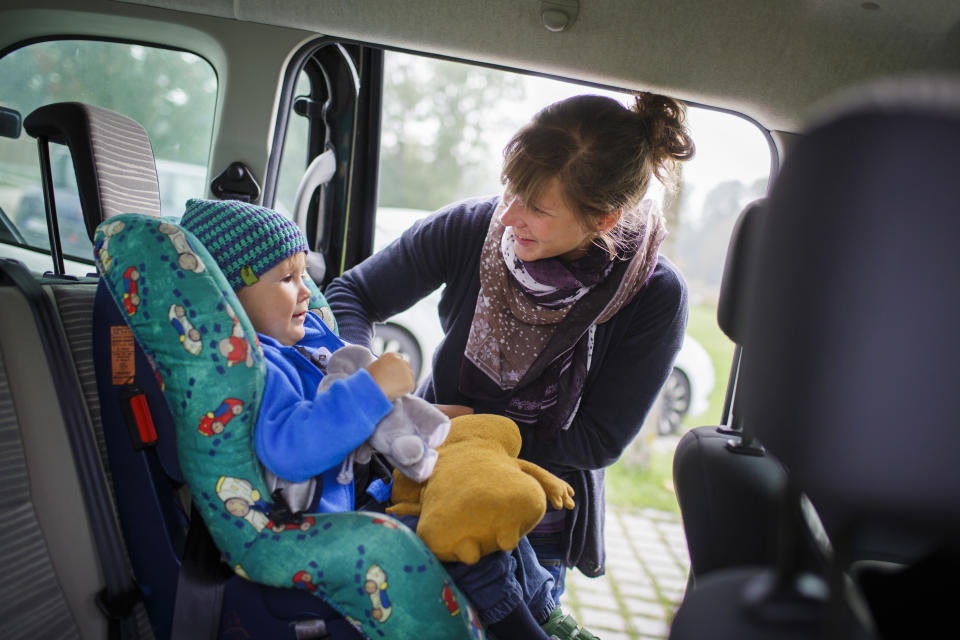 MARZLING, GERMANY - SEPTEMBER 27: Mother is fastening the seat belt of her son in the back of a car. (Photo by Thomas Trutschel/Photothek via Getty Images)