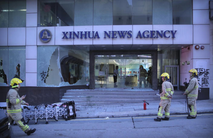 Firefighters stand outside the offices of China's Xinhua News Agency after its windows were shattered during protests in Hong Kong, Saturday, Nov. 2, 2019. Hong Kong riot police fired multiple rounds of tear gas and used a water cannon Saturday to break up a rally by thousands of masked protesters demanding meaningful autonomy after Beijing indicated it could tighten its grip on the Chinese territory. (AP Photo/Kin Cheung)