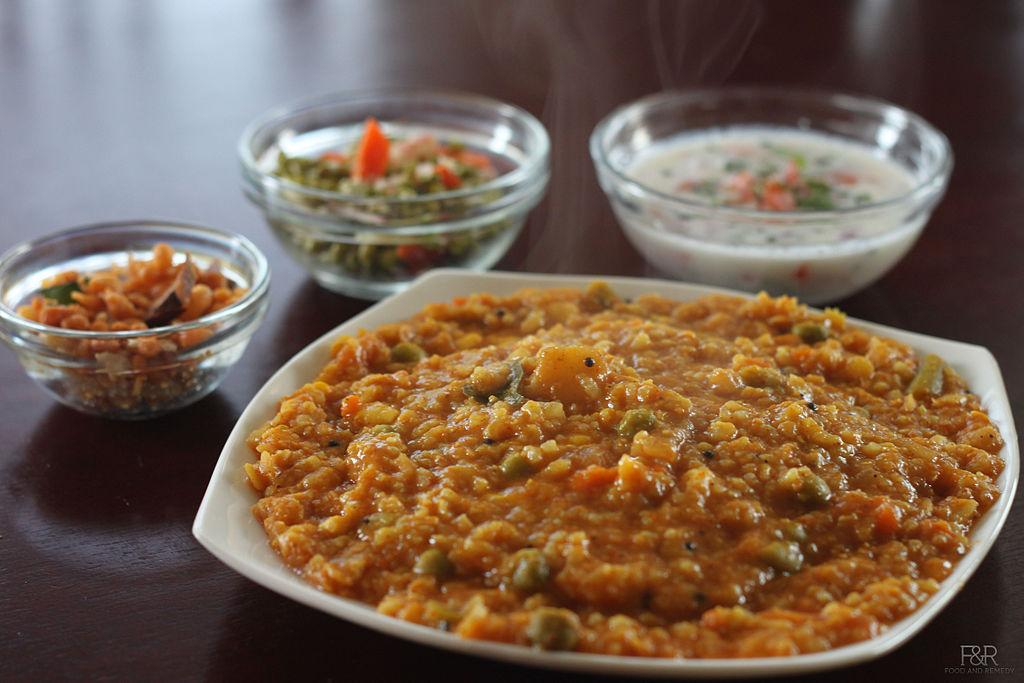 "<p>A traditional Karnataka rice preparation, this dish can be relished hot, topped with ghee. Soak 1 cup rice and 3/4 th cup dal (toor dal/arhar dal) separately for half an hour and drain them. Heat some oil in a pressure cooker. Add 2 chopped onion and sauté them. Add 2-3 green chillies, curry leaves and turmeric powder. Add rice and dals with 4-5 cups of water. Bring to a boil. To this add chopped vegetables like drum sticks, potatoes, french beans, capsicum, some chopped tomatoes, asafoetida, red chilli powder, tamarind pulp and salt. Stir well and add bisi bele bhaat masala. Cover and pressure cook till soft. Continue cooking on slow flame for 5 minutes. Stir once it cools down. Some water can be added to loosen the consistency. ""Creative Commons Bisi bele bath"" by Food and Remedy is licensed under CC BY 3.0  </p>"