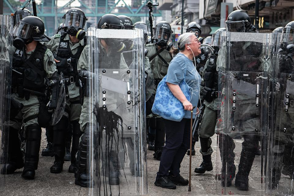 A woman shouts at police officers as they advance towards protesters in the district of Yuen Long. Photo: Laurel Chor/Getty Images