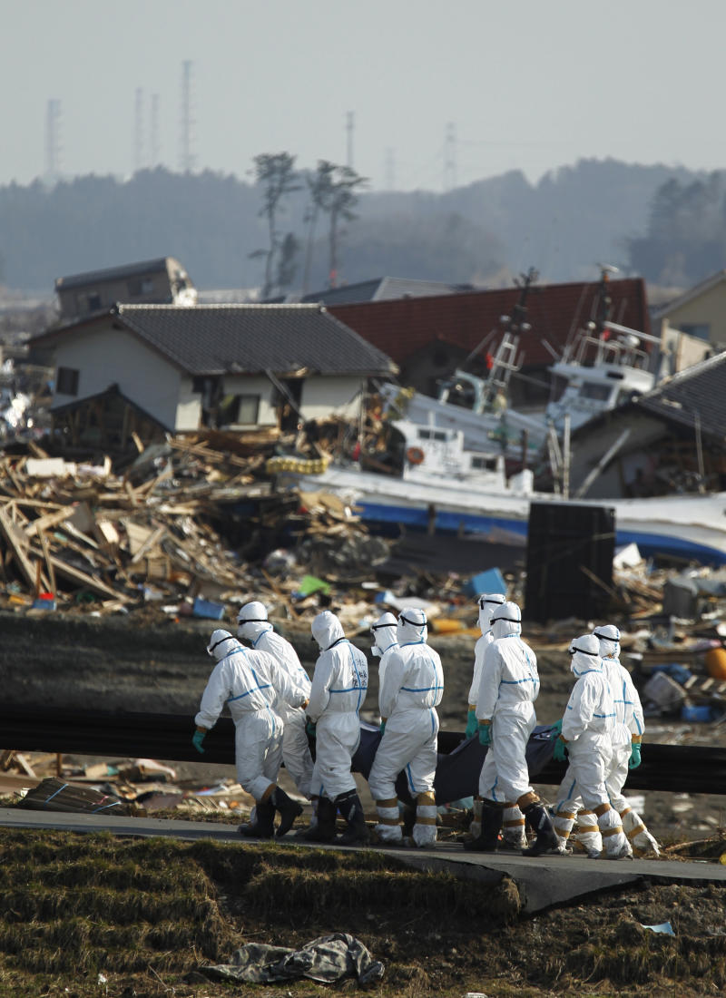 Japanese police officers carry a body during a search and recovery operation for missing victims in the area devastated by the March 11 earthquake and tsunami in Namie, Fukushima Prefecture, northeastern Japan, Friday, April 15, 2011. In the background is part of the Fukushima Dai-ichi nuclear complex.(AP Photo/Hiro Komae)