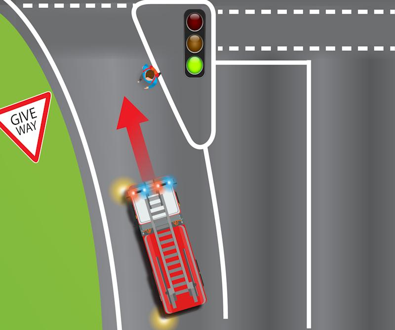 A man approaches a give way crossing as a fire truck with sirens approaches.
