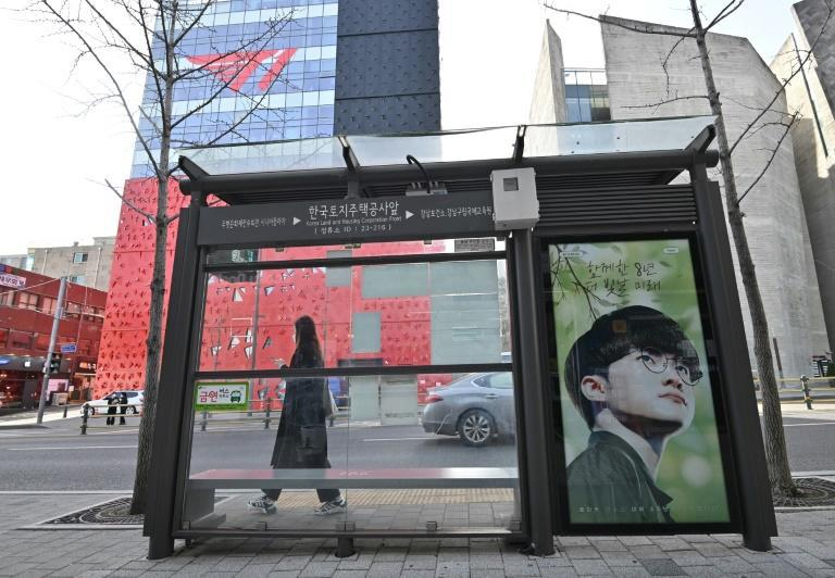 A billboard featuring League of Legends giant Faker is seen on a bus stop in front of the T1 building